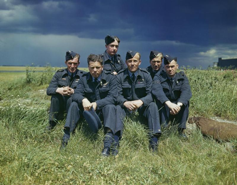 The_crew_of_Lancaster_AJ-T_sitting_on_the_grass,_posed_under_stormy_clouds